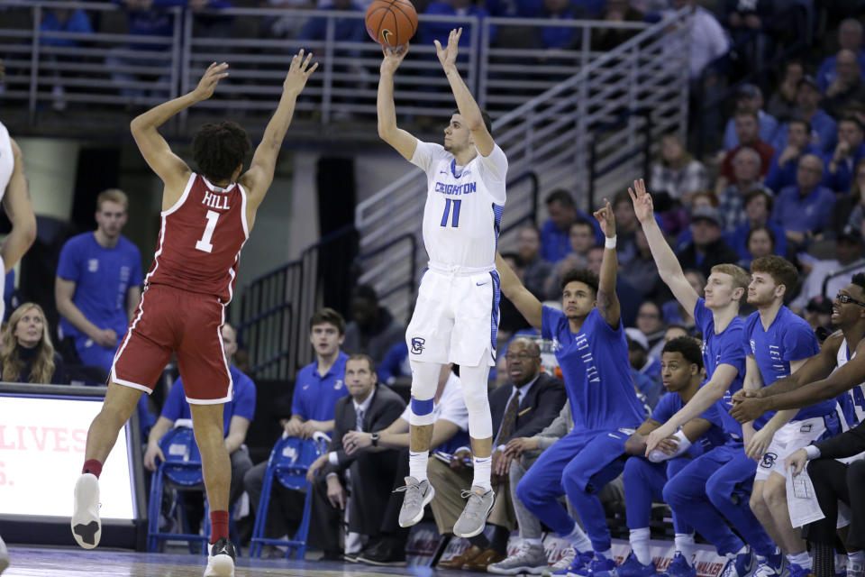 """FILE - Creighton's Marcus Zegarowski (11) shoots for three points against Oklahoma's Jalen Hill (1) during the second half of an NCAA college basketball game in Omaha, Neb., in this Tuesday, Dec. 17, 2019, file photo. Zegarowski announced he's leaving Creighton and declaring for the NBA draft, the biggest name in an exodus that started after the Bluejays' run to the NCAA Sweet 16. """"I will be entering the 2021 NBA draft and look forward to continuing to work hard, chase my dreams and play the game I love,"""" Zegarowski tweeted Tuesday, April 13, 2021. """"Thank you Creighton for making my college experience so special. I will forever be a Bluejay."""" (AP Photo/Nati Harnik, File)"""