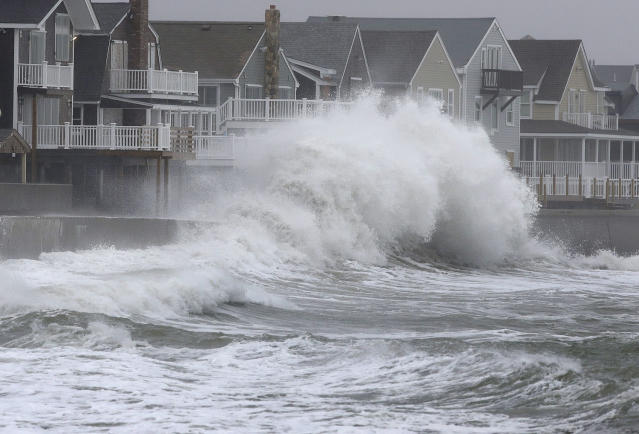 <p>Waves crash against a seawall and houses in Scituate, Mass., on March 7, 2018. (Photo: Steven Senne/AP) </p>