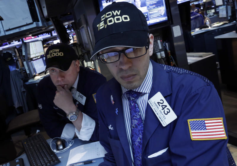 """Specialists Devin Cryan, left, and Gabriel Freytes wear a """"Dow 15,000"""" hats as they work at a post on the floor of the New York Stock Exchange Friday, May 3, 2013. A big gain in the job market is lifting the stock market to a record high. The Dow Jones industrial average crossed 15,000 for the first time, and the Standard and Poor's 500 index, a broader market measure, rose above 1,600.(AP Photo/Richard Drew)"""