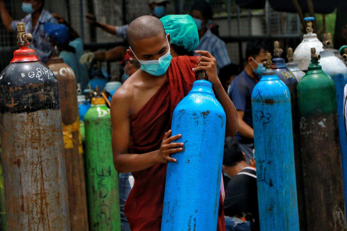 FILE - In this July 28, 2021, file photo, Buddhist monk wearing a face mask holds an oxygen tank for refill outside the Naing oxygen factory at the South Dagon industrial zone in Yangon, Myanmar. Supplies of medical oxygen are running low, and the government has put restrictions on its private sale in many places, saying it is trying to prevent hoarding. (AP Photo, File)