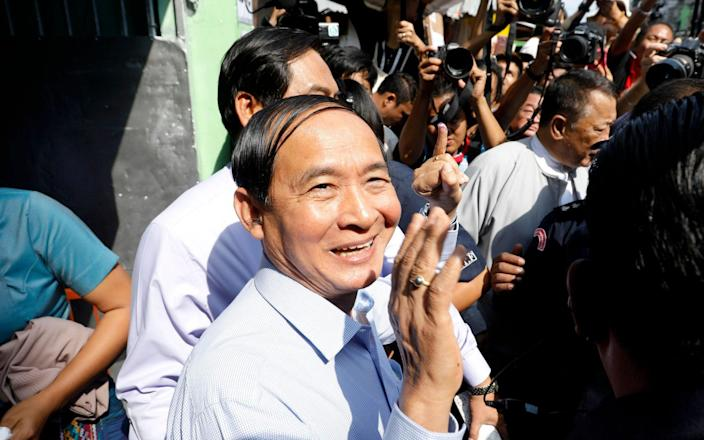 Myanmar president Win Myint (C) greets his supporters after voting at a polling station of Tarmwe township during by-elections in Yangon - EPA