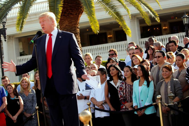 FILE PHOTO: Trump employees stand behind him in support at a campaign event at his Trump National Doral golf club in Miami, Florida