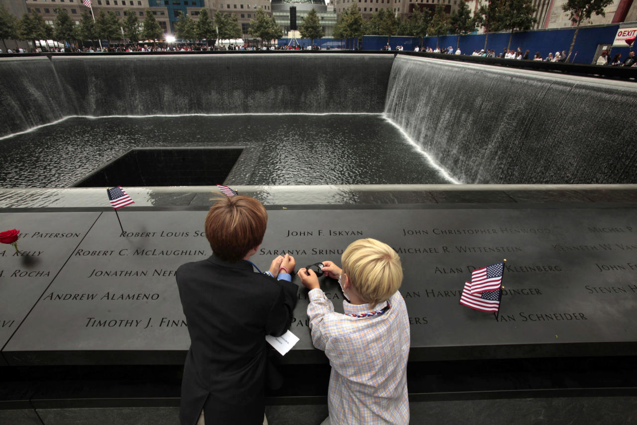 Finn Straine, 12, left, and his brother Charlie Straine, 10, stand by the name of their father, James Straine Jr., who worked for Cantor Fitzgerald and died in the Sept. 11, 2001 World Trade Center attacks, as they attend the 10th anniversary ceremonies at the National September 11 Memorial, Sunday, Sept. 11, 2011, in New York. (AP Photo/Carolyn Cole, Pool)