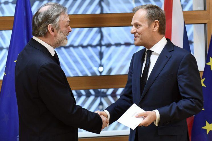 EU Council President Donald Tusk shakes hands with UK Permanent Representative to the EU Tim Barrow as he hands over Theresa May's letter (AP Images)