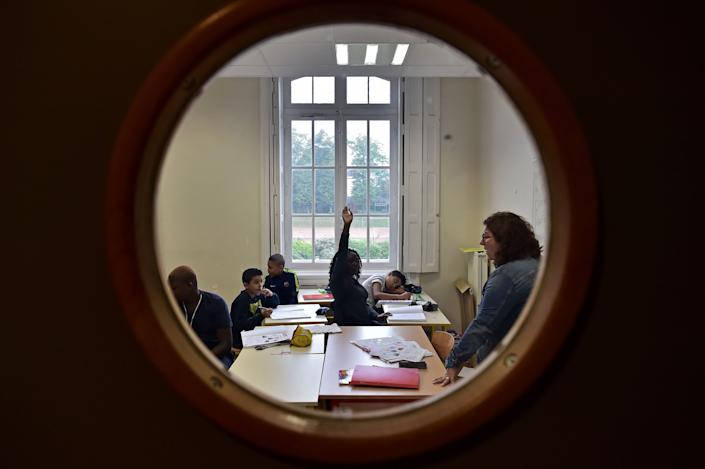 High school students attend a class.  (Photo credit to read CHRISTOPHE ARCHAMBAULT / AFP via Getty Images)