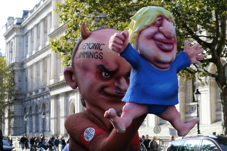 Demonstrators brandish an effigy depicting Britain's Prime Minister Boris Johnson as a puppet operated by his adviser Dominic Cummings during an anti-Brexit protest
