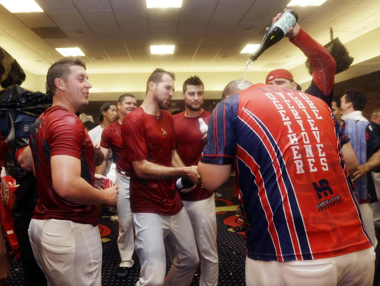 St. Louis Cardinals pour sparkling wine over Matt Adams, foreground, as they celebrate after defeating the Pittsburgh Pirates 6-1 in Game 5 of a National League baseball division series, Wednesday, Oct. 9, 2013, in St. Louis. The Cardinals advanced to the NL championship series against the Los Angeles Dodgers. (AP Photo/Jeff Roberson)