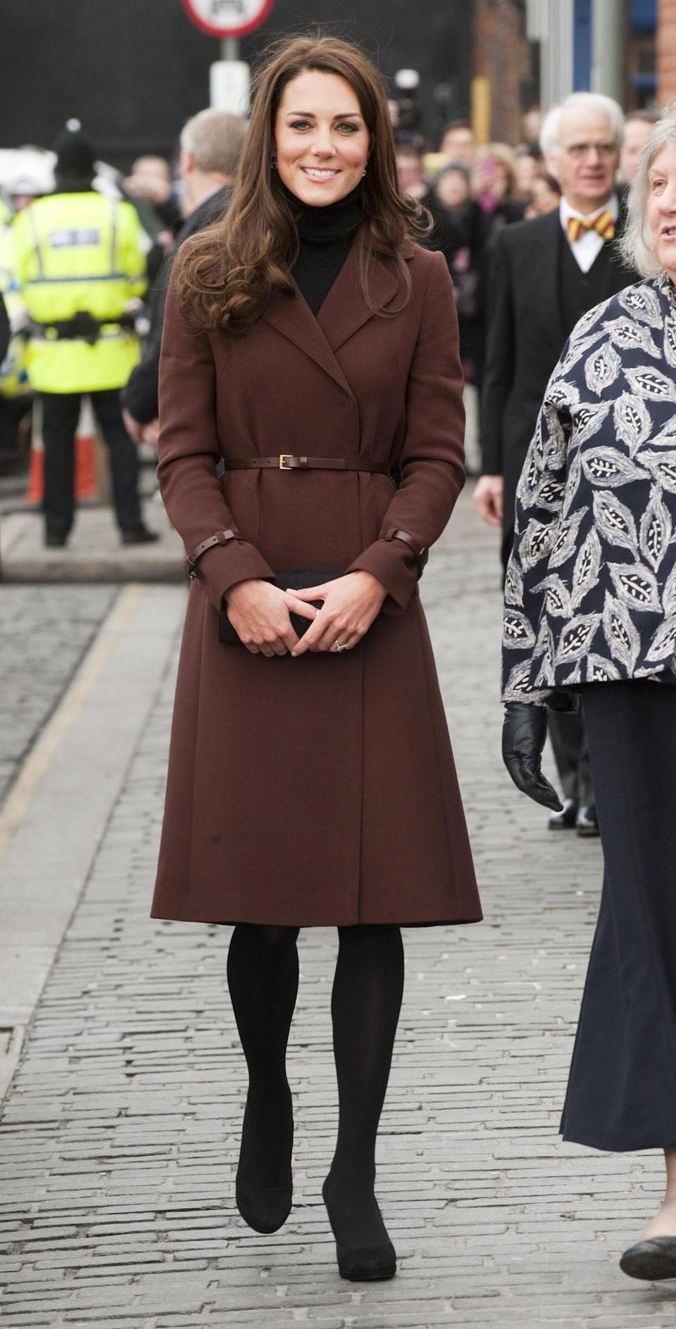 <p>Kate visited Liverpool wearing a chic brown Hobbs coat worn with a black knee length Oasis dress. She paired the look with black tights, a Stuart Weitzman clutch and and matching shoes. </p><p><i>[Photo: PA]</i></p>