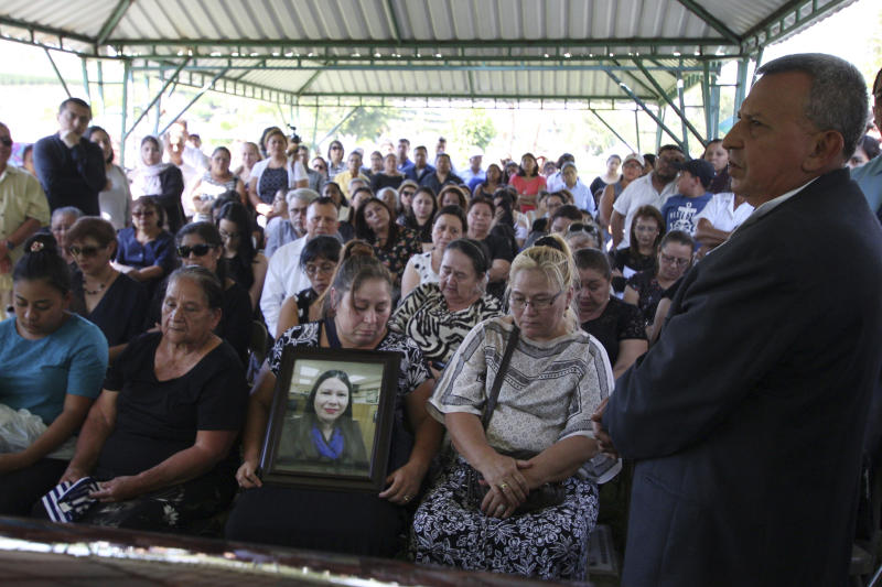 FILE - In this April 17, 2018 file photo, Demetrio Turcios, right, father of slain journalist Karla Turcios, addresses people attending Karla's funeral at the cemetery in San Salvador, El Salvador. The 33-year-old journalist, who worked for the magazine El Economista, owned by the La Prensa Grafica, was kidnapped on Saturday from her home and her body was found hours later on a highway. (AP Photo/Salvador Melendez, File)