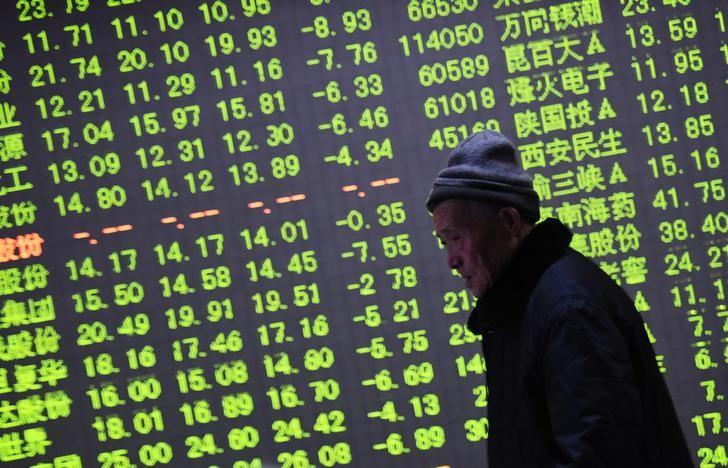 An investor walks past an electronic screen showing stock information at a brokerage house in Hangzhou