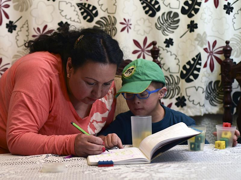 Colombian priest Aida Soto helps her son with his homework in Bogota on March 5, 2015. Soto is one of four Latin American women priests, member of the Roman Catholic Women Priests Association: LUIS ACOSTA/Getty/AFP