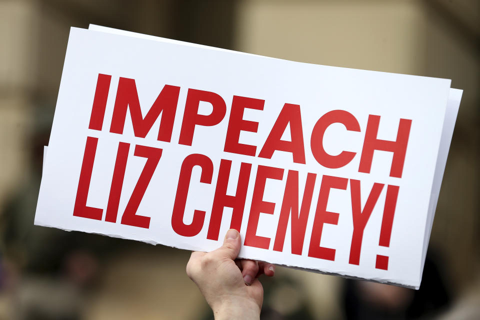 A protester holds a sign reading, in red block letters,