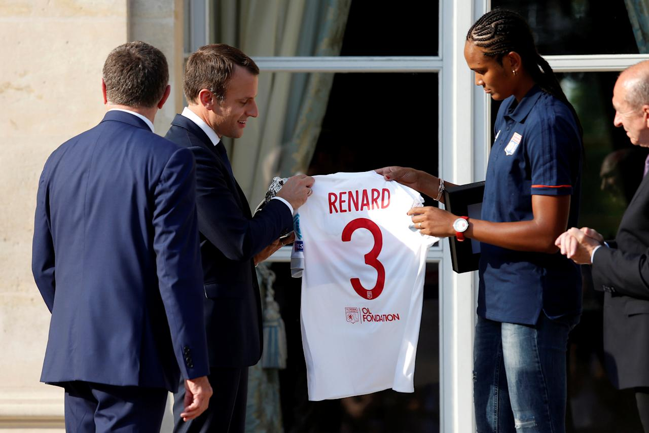 French President Emmanuel Macron (2ndL) holds a jersey presented by Lyon's captain Wendie Renard (R) during a ceremony at the Elysee Palace in Paris, France, June 20, 2017 to celebrate their victory in the UEFA Women's Champions League soccer tournament.    REUTERS/Geoffroy van der Hasselt/Pool