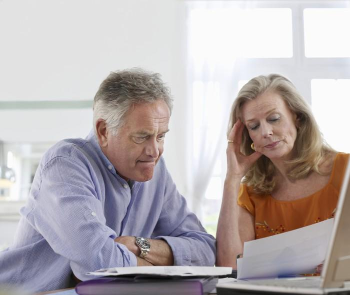 A visibly concerned mature couple examining their finances.