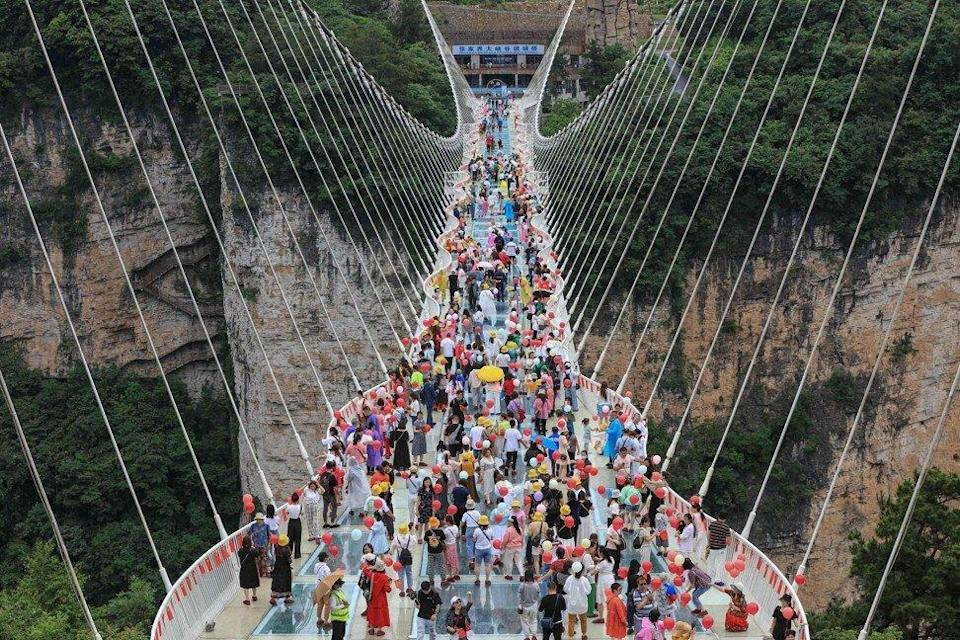 An aerial photo taken on June 20, 2021 shows people walking on a glass skywalk in Zhangjiajie in central Hunan province. Photo: AFP