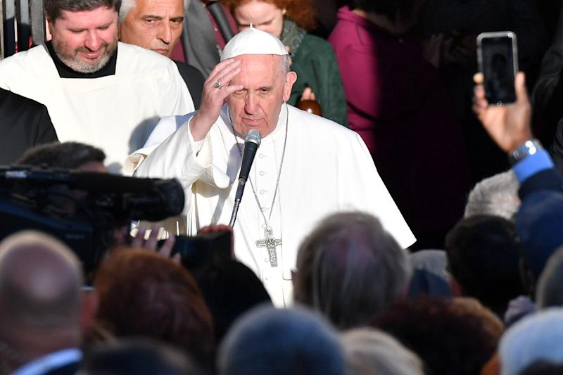 "Pope Francis blesses the crowd as he leaves the Basilica of St. Bartholomew on Tiber Island after the Liturgy of the Word with the Community of Sant'Egidio in memory of the ""New Martyrs"" of the 20th and 21th century, on April 22, 2017 in Rome (AFP Photo/Alberto PIZZOLI)"