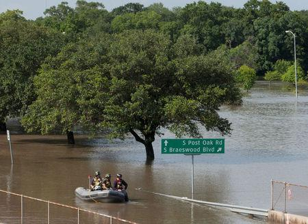 Rescue personnel search the floodwaters along Brays Bayou in southwest Houston, Texas May 26, 2015. REUTERS/Daniel Kramer