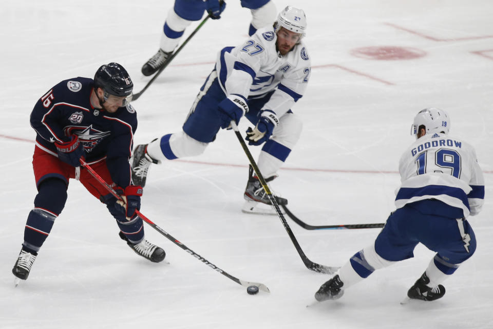 Columbus Blue Jackets' Max Domi, left, carries the puck as Tampa Bay Lightning's Ryan McDonagh, center, and Barclay Goodrow during the second period of an NHL hockey game Thursday, Jan. 21, 2021, in Columbus, Ohio. (AP Photo/Jay LaPrete)