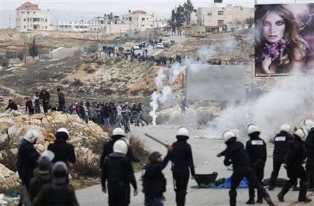 Palestinian policemen stand in front of demonstrators outside the Jalazoun refugee camp near Ramallah