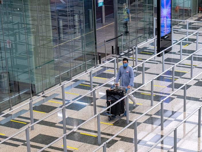 <br>A traveller wearing a face mask walk towards the taxi stand at the arrival hall of Changi Airport on March 23, 2020 in Singapore