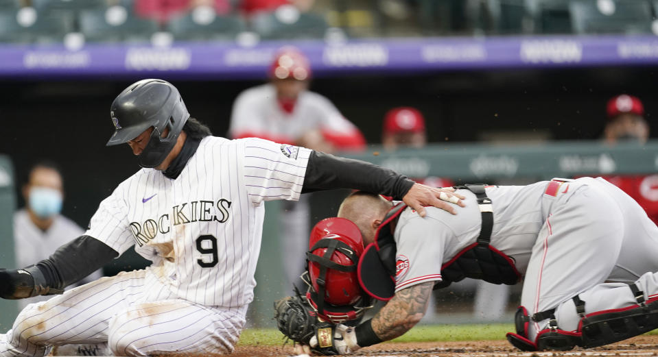 Cincinnati Reds catcher Tucker Barnhart, right, tags out Colorado Rockies' Connor Joe, who tried to score on a ground ball hit by Ryan McMahon during the first inning of a baseball game Thursday, May 13, 2021, in Denver. (AP Photo/David Zalubowski)