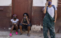 People wear masks during the COVID-19 pandemic outside a grocery store where they wait for it to open in Havana, Cuba, Tuesday, Oct. 12, 2021. (AP Photo/Ramon Espinosa)
