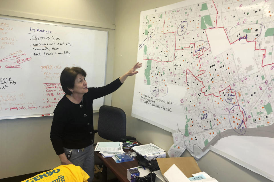 In this Nov. 22, 2019 file photo, Detroit 2020 Census Campaign executive director Victoria Kovari looks over a Detroit map showing city neighborhoods that were under-counted in the 2010 census. Michigan's slow population growth over the past decade will cost the state a U.S. House seat, continuing a decades-long trend as job-seekers and retirees have fled to other states. (AP Photo/Corey Williams)