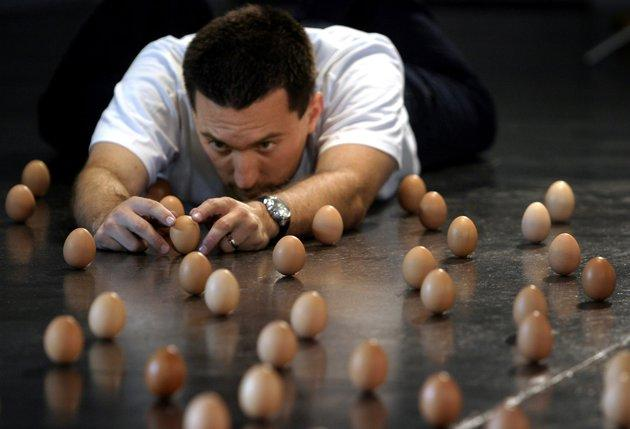 Brian Spotts of the U.S. works to balance 439 eggs on their ends on the floor of the Australian Centre for Contemporary Art in Melbourne September 14, 2005. Spotts, who lives in Colorado, travelled to Melbourne to attempt a new world egg balancing record which currently stands at 420 eggs. REUTERS/James Bodington/Handout