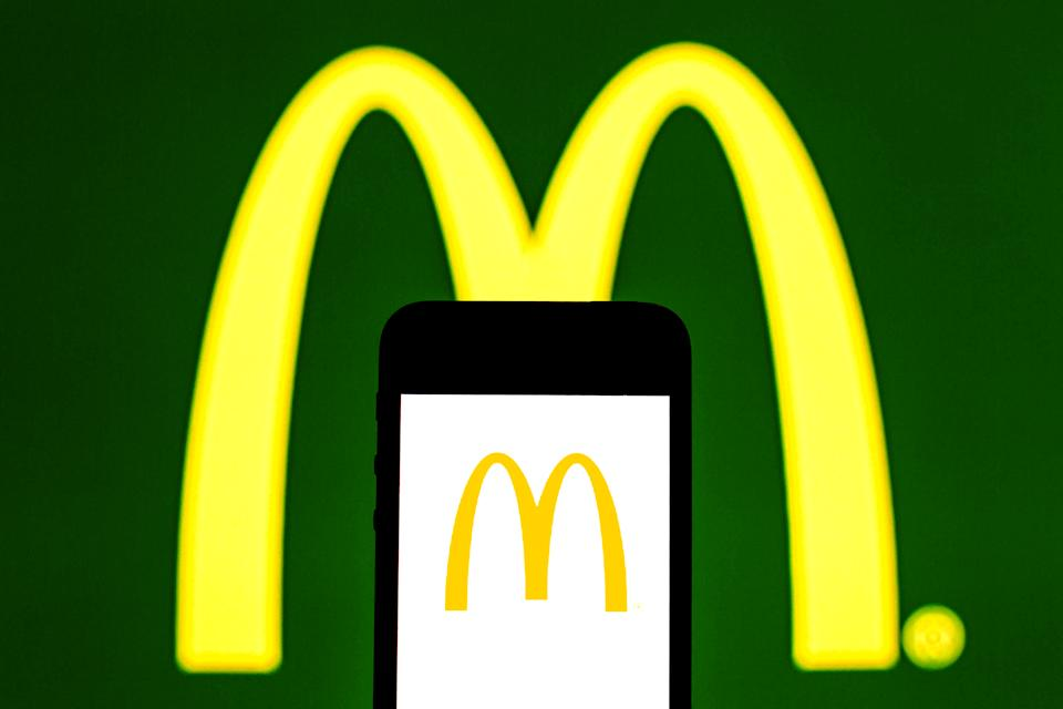 SPAIN - 2021/07/31: In this photo illustration, a McDonald's logo seen displayed on a smartphone and in the background. (Photo Illustration by Thiago Prudencio/SOPA Images/LightRocket via Getty Images)