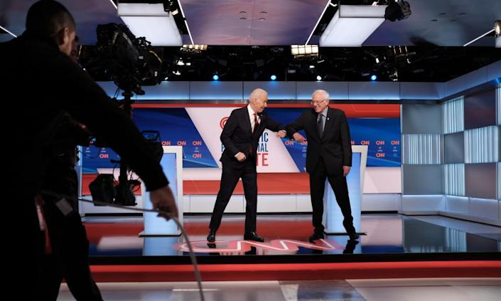 """<span class=""""element-image__caption"""">Joe Biden and Bernie Sanders greet each other with their elbows at the last Democratic presidential debate, in Washington. Sanders has been forced to cancel the rallies that are a pillar of his campaign.</span> <span class=""""element-image__credit"""">Photograph: Gabriella Demczuk For Cnn/EPA</span>"""
