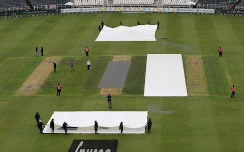 General view of officials and groundstaff on the pitch as rain delays play  - Credit: Reuters