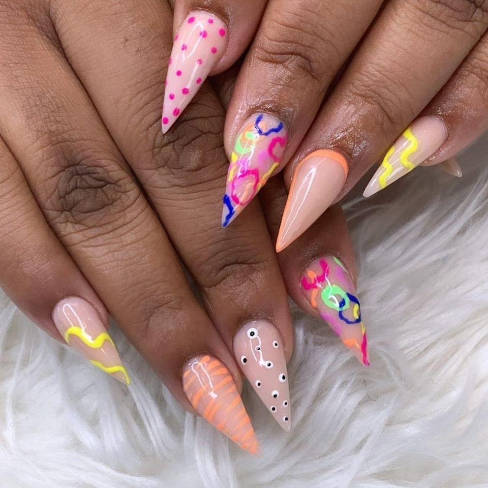 """Painting your nails all one color is so yesterday. Nowadays, people like to play around with different designs on each finger, like this mismatched manicure created by Brooklyn-based <a href=""""https://www.instagram.com/badgal.nails/"""" rel=""""nofollow noopener"""" target=""""_blank"""" data-ylk=""""slk:Jasmine Lewis"""" class=""""link rapid-noclick-resp"""">Jasmine Lewis</a>. We can't decide which nail we like the best, but the way she incorporated bright yellow, orange, pink, green, and blue hues is impressive."""