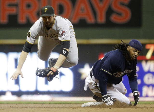 Pittsburgh Pirates second baseman Neil Walker leaps over Milwaukee Brewers' Rickie Weeks to turn a double play on a ball hit by Milwaukee Brewers' Ryan Braun during the eighth inning of a baseball game Wednesday, May 14, 2014, in Milwaukee. (AP Photo/Morry Gash)