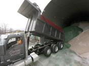 A fresh load of salt is delivered and put in the storage shed in the Pittsfield, Mass., city yards before as a snow storm looms, Wednesday, Dec. 16, 2020. The green salt is treated for ultra-low temperatures. (Ben Garver/The Berkshire Eagle via AP)