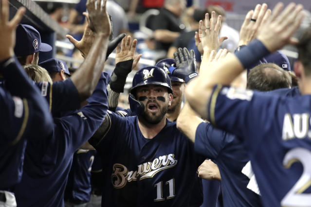 Milwaukee Brewers' Mike Moustakas (11) is congratulated after hitting a two run home run during the ninth inning of a baseball game against the Miami Marlins, Wednesday, Sept. 11, 2019, in Miami. The Brewers won 7-5. (AP Photo/Lynne Sladky)