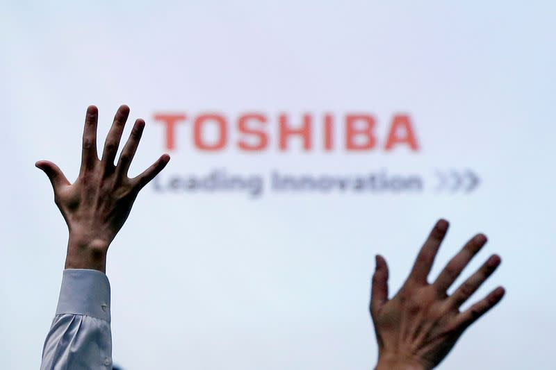 FILE PHOTO: Reporters raise their hands for a question during a news conference by Toshiba Corp CEO Satoshi Tsunakawa at the company headquarters in Tokyo
