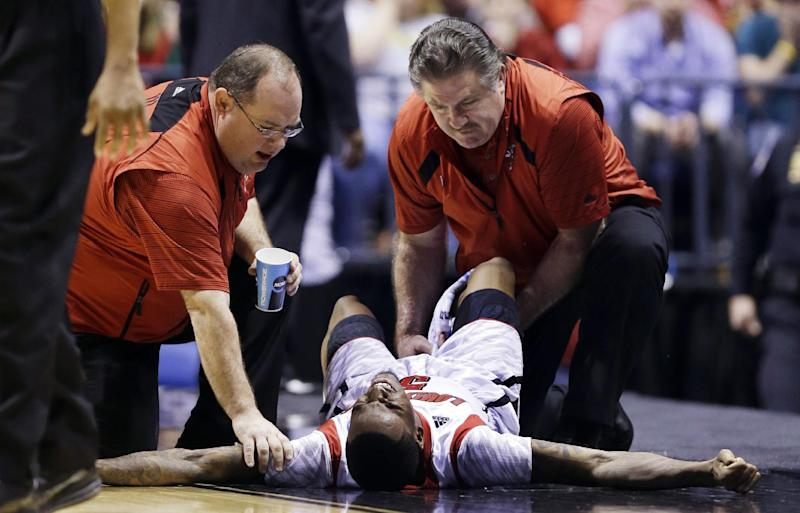 AP10ThingsToSee - Trainers check on Louisville guard Kevin Ware after he broke his leg during the first half of the Midwest Regional final against Duke in an NCAA college basketball tournament, Sunday, March 31, 2013, in Indianapolis. (AP Photo/Michael Conroy, File)