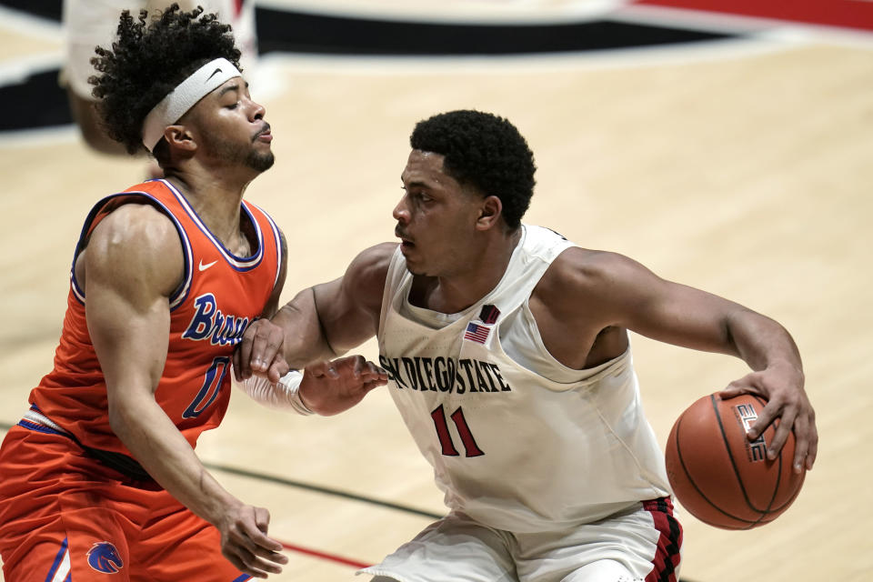 San Diego State forward Matt Mitchell (11) drives the ball against Boise State guard Marcus Shaver Jr. (0) during the first half of an NCAA college basketball game Saturday, Feb 27, 2021, in San Diego. (AP Photo/Gregory Bull)