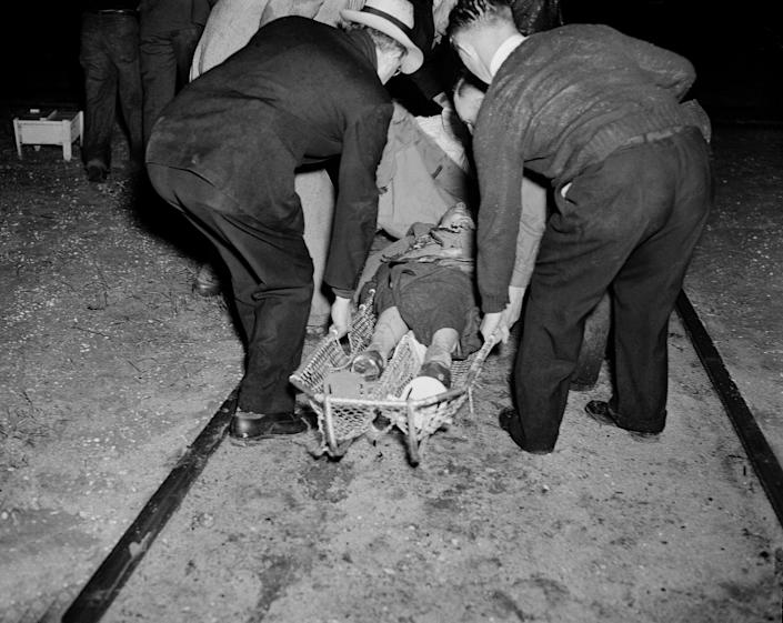 <p>A victim of the Hindenburg disaster is taken away in a stretcher in the aftermath of the airship crash in Lakehurst, N.J., May 6, 1937. The German-built zeppelin burst into flame in mid-air as it was landing after its transatlantic voyage, carrying 97 passengers and crew. Thirty-five people on board and one ground crew member were killed. (AP Photo/Murray Becker) </p>
