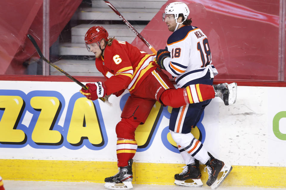 Edmonton Oilers' James Neal, right, hits Calgary Flames' Jusso Valimaki during the first period of an NHL hockey game Saturday, April 10, 2021, in Calgary, Alberta. (Larry MacDougal/The Canadian Press via AP)