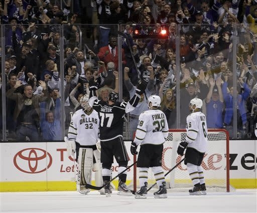 Los Angeles Kings' Jeff Carter(77) celebrates his goal against Dallas Stars goalie Kari Lehtonen(32) as Dallas Stars' Vernon Fiddler(38) and Trevor Daley look on during overtime of an NHL hockey game in Los Angeles, Sunday, April 21, 2013. The Kings won 4-3 in overtime. (AP Photo/Jae C. Hong)