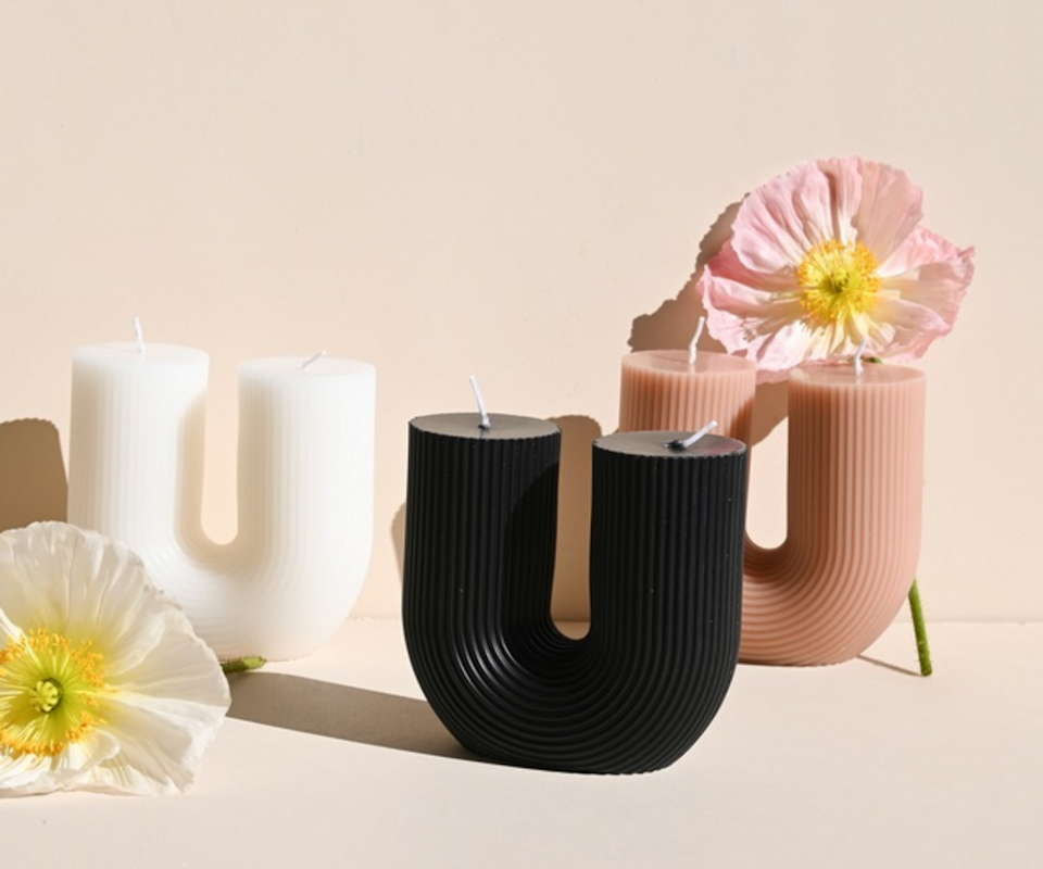 Three white, black and blush u-shaped candles in front of a pale pink background with a yellow and pale pink flower either side.