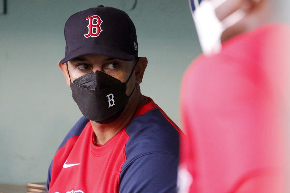 Boston Red Sox manager Alex Cora (13) looks out from the dugout before the start of the baseball game against the Cleveland Indians at Fenway Park, Friday, Sept. 3, 2021, in Boston. (AP Photo/Mary Schwalm)