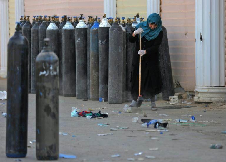 An Iraqi woman cleans debris next to evacuated oxygen bottles outside the Ibn al-Khatib Hospital in Baghdad, on April 25 after a fire broke out there killing at least 23 people