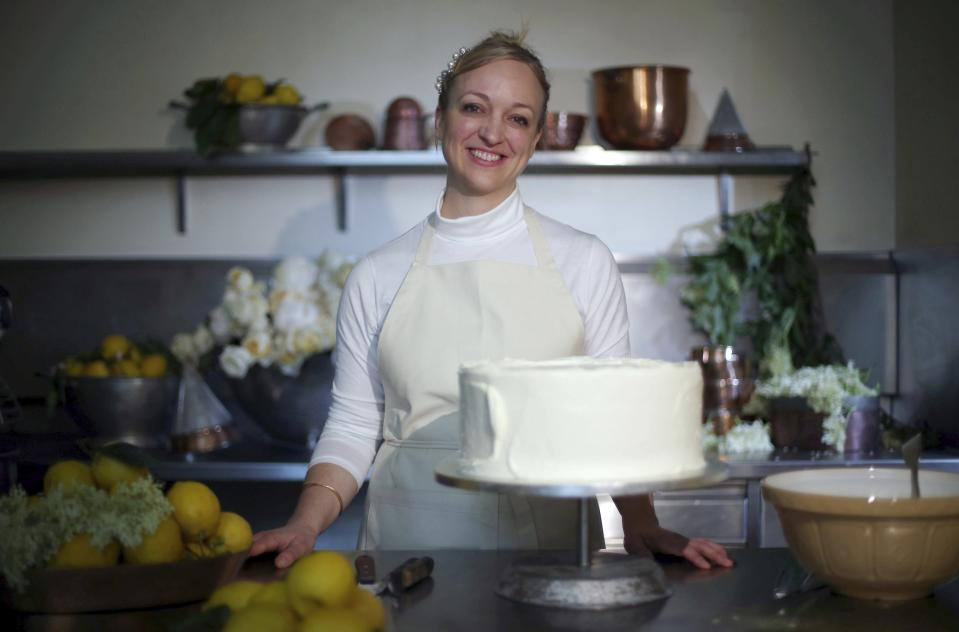 Claire Ptak poses for a photograph with a tier of the cake for the wedding.