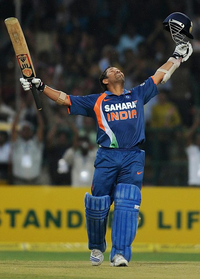 TO GO WITH Cricket-Asia-year-2010 by Kuldip Lal (FILES) In a file picture taken on February 24, 2010 Indian cricketer Sachin Tendulkar throws his arms up into the air as he celebrates scoring a world record breaking double century (200 runs) during the second One Day International (ODI) cricket match at the Captain Roop Singh Stadium in Gwalior. Sachin Tendulkar's magnificent batting form and an unsavoury match-fixing scandal swirling around Pakistan provided the highs and lows for Asian cricket in the year gone by. The master tore South Africa's frontline attack to shreds in April to hit one-day cricket's first double-century, and took the same form into the traditional five-day format.  AFP PHOTO/ MANAN VATSYAYANA (Photo credit should read MANAN VATSYAYANA/AFP/Getty Images)