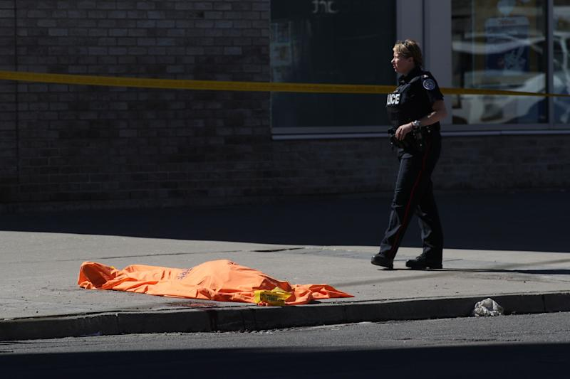 A member of the police stands next to an unidentified body near the crime scene.