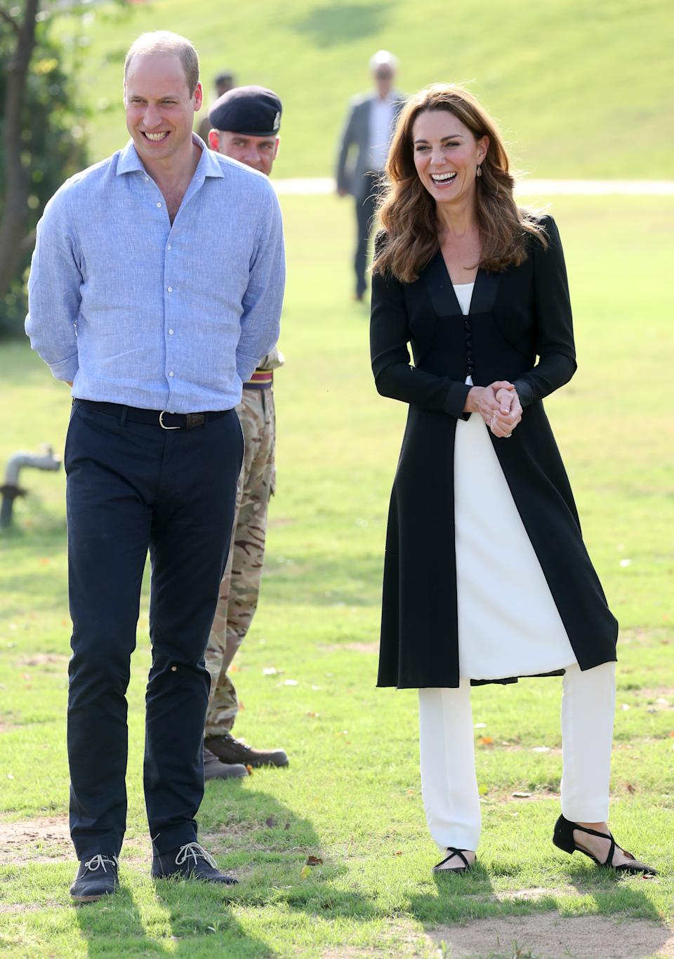 """For the final engagement of the tour, Kate wore a long black jacket by <a href=""""https://fave.co/32pDAx6"""" rel=""""nofollow noopener"""" target=""""_blank"""" data-ylk=""""slk:Beulah London"""" class=""""link rapid-noclick-resp"""">Beulah London</a>, which was from the brands 2014 collection. She paired it with <a href=""""https://fave.co/2MMzGHY"""" rel=""""nofollow noopener"""" target=""""_blank"""" data-ylk=""""slk:£195 Russell & Bromley crossover flats"""" class=""""link rapid-noclick-resp"""">£195 Russell & Bromley crossover flats</a>. [Photo: Getty]"""
