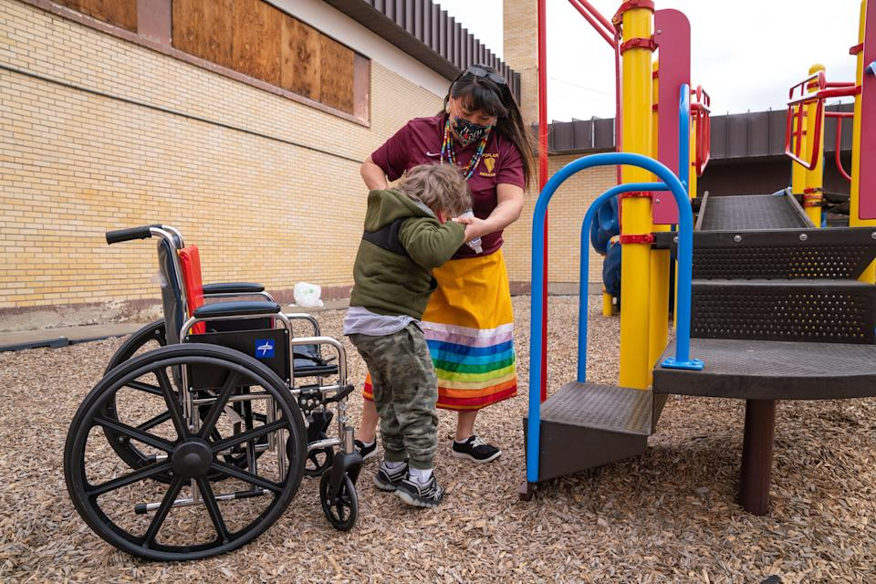 Shari Daniels helps a student get out of his wheelchair during recess at Poplar Elementary School. Daniels worked with students with disabilities as a teacher's aide before completing formal training to teach in her hometown.