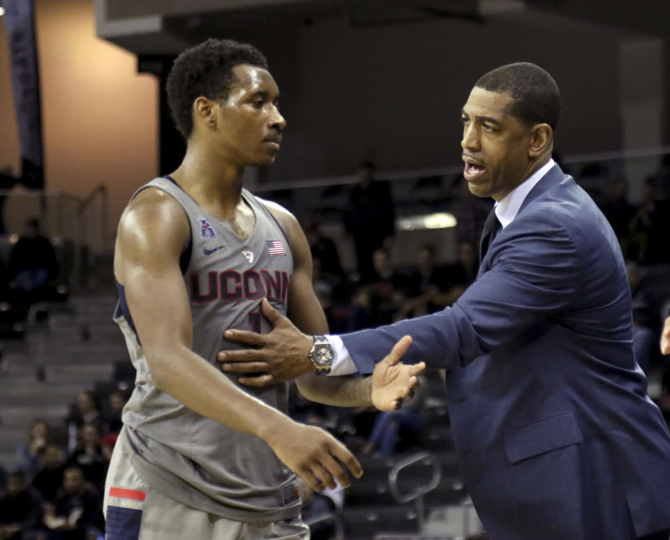 FILE - Connecticut head coach Kevin Ollie, right, talks with Christian Vital during the second half of an NCAA college basketball game against Cincinnati in Highkland Heights, Ky., in this Thursday Feb. 22, 2018, file photo. Former Connecticut head coach Kevin Ollie has been brought on board in a leadership role for a new basketball league designed to offer elite high school players another pathway to the pros. Ollie will serve as coach and director of player development for Overtime Elite, which markets itself to 16-to-18 year old players with guarantees of academic education and a six-figure salary. (AP Photo/Tony Tribble, File)